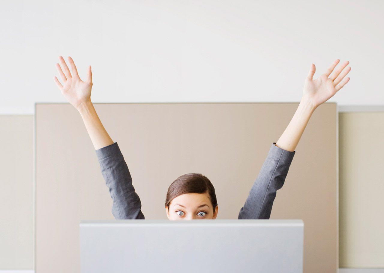 Eine junge Frau sitzt hinter einem Computerbildschirm und reißt freudig die Hände in die Luft. Die untere Hälfte ihres Gesichts ist durch den Bildschirm verdeckt.