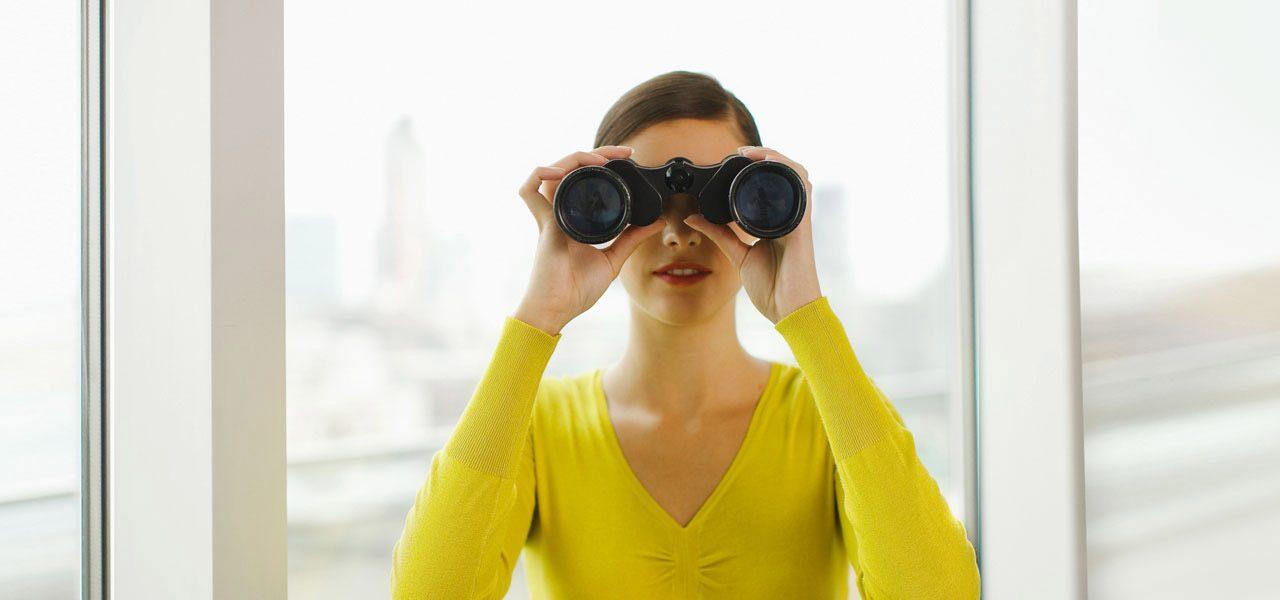 Eine junge Frau steht im Zimmer und schaut durch ein Fernglas in Richtung des Betrachters bzw. der Betrachterin.